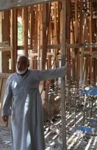 Egyptian clergyman amid church building damaged in Islamist attack. (Morning Star News photo)