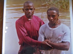 A photo of the Rev. James Danladi Mahwash baptizing Jamle Benjamin Sunday, who was killed in the attack in Mile Bakwai, Nigeria. (Morning Star News photo)