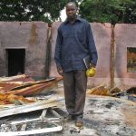 The Rev. John Dakwat in the ruins of his church building. (Morning Star News photo)