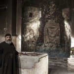 Priest examining damaged church building in Minya Governorate, Egypt. (Watani)