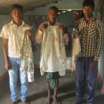 Irma Markami and his sons with bloodied and torn clothing. (Morning Star News)
