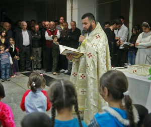A priest conducts mass for displaced people in office complex in Erbil, Iraq. (Morning Star News)
