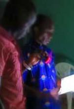 A pastor leads a Christian meeting by flashlight at damaged church building in Niamey, Niger. (RUN International).jpg