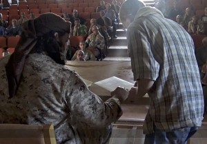 Islamic State member gives Dhimma (second-class) contracts for Christians to sign. (Islamic State)