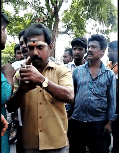 Extremist with ash mark of Hindu devotion on his forehead checks phone after stopping children going to Vacation Bible School in Ratnapuri, India. (Morning Star News)