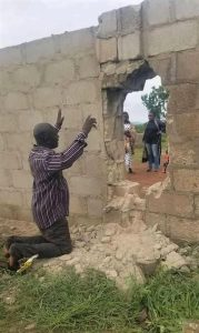 A parent prays for students abducted through breached wall at Bethel Baptist High School, Maraban Rido, Kaduna state, Nigeria on July 5, 2021. (Vincent Bodam for Morning Star News)