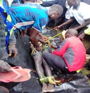 Area residents untie the body of Dante Tambika on shore of Lake Lemwa, Uganda on Sept. 1, 2021. (Morning Star News)